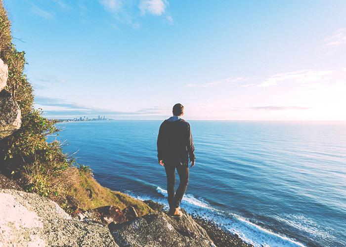 man-standing-on-coast-on-cliff