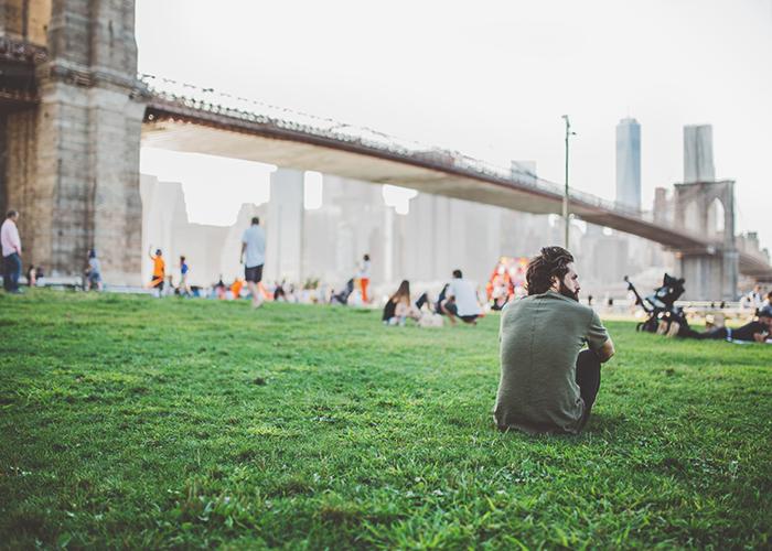 man-sitting-on-green-lawn-under-bridge